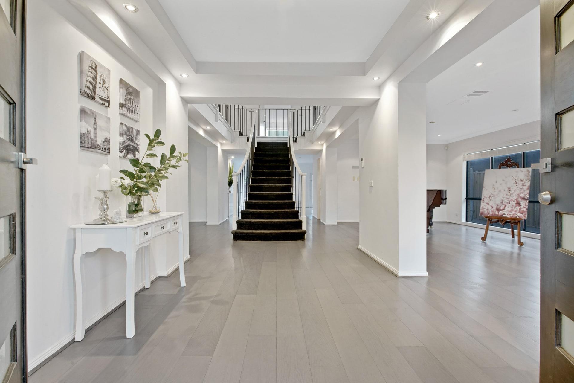 Photographie HDR de l'entrée d'un maison avec un escalier en arrière-plan.