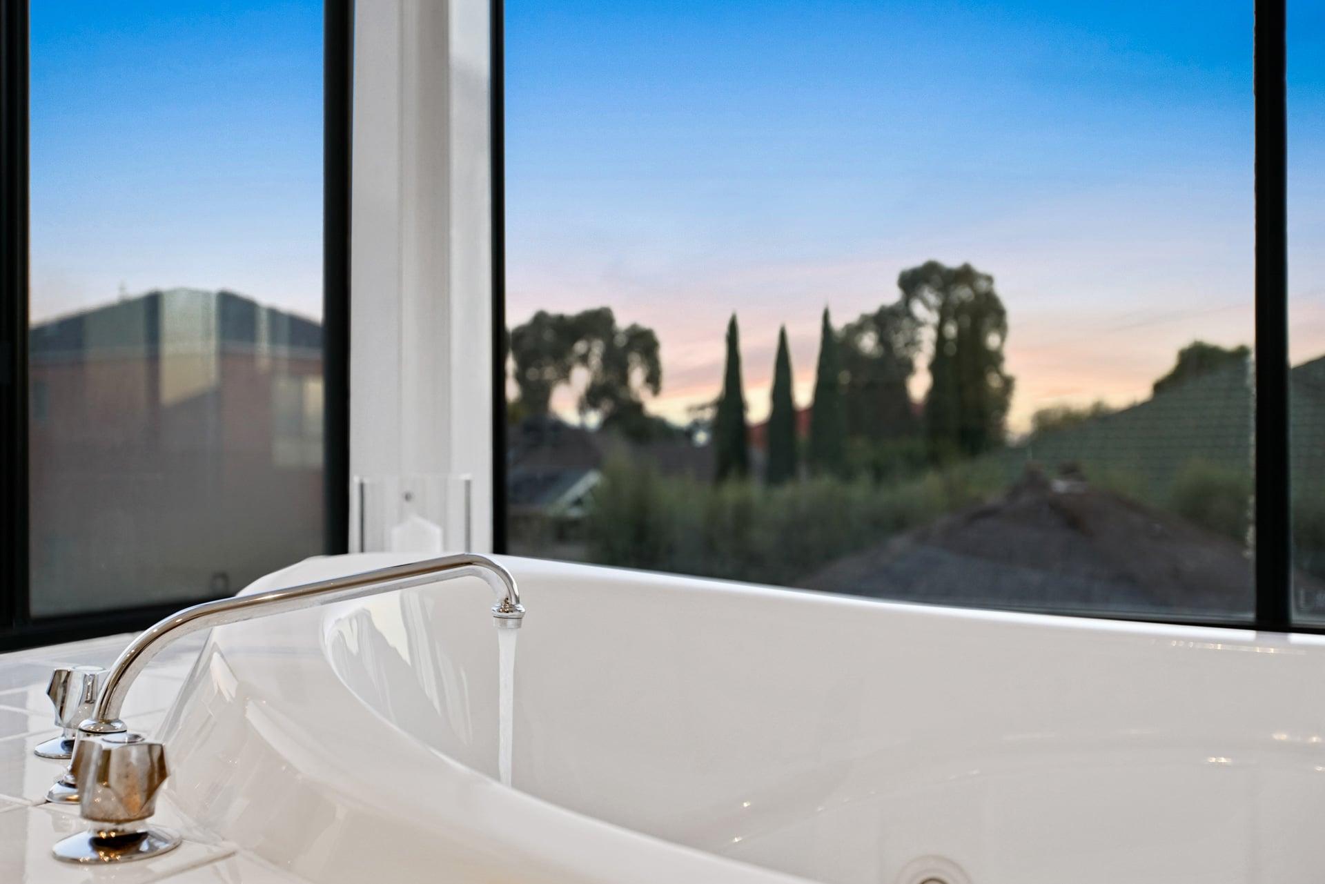 Photographie HDR d'une baignoire avec une vue sur l'extérieur.