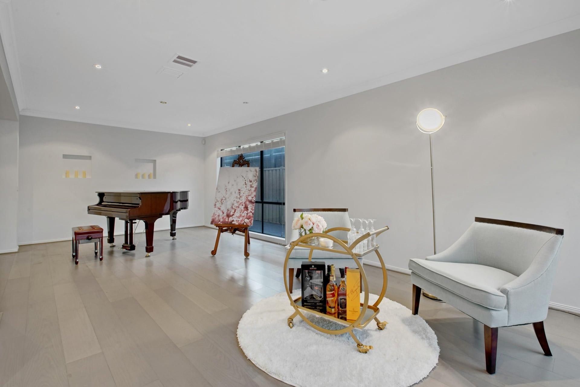 Photographie HDR du salon d'une maison. Un piano à queue est au fond de la pièce.