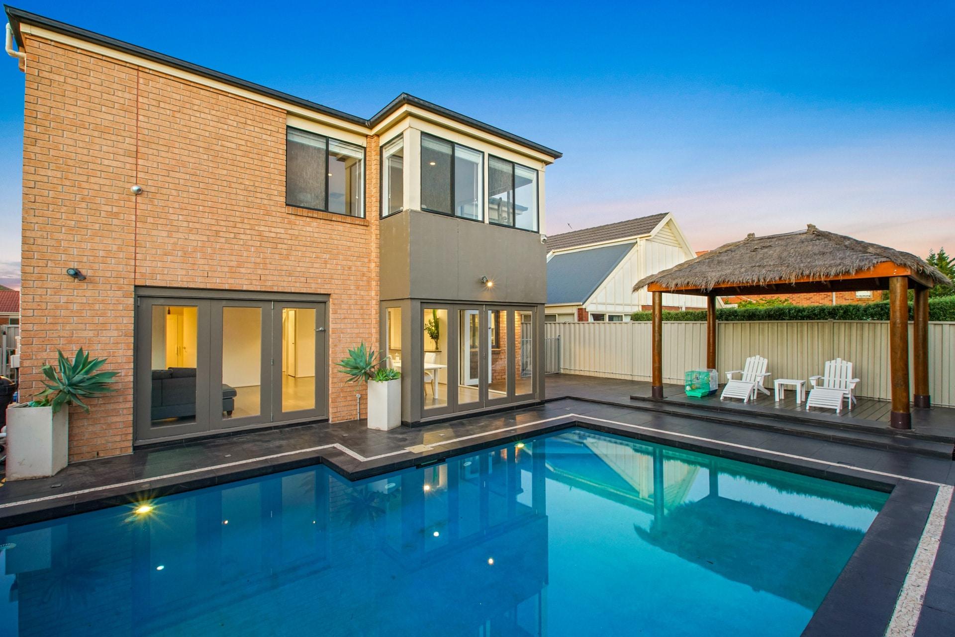 Photo immobilière HDR du jardin avec piscine d'une maison.