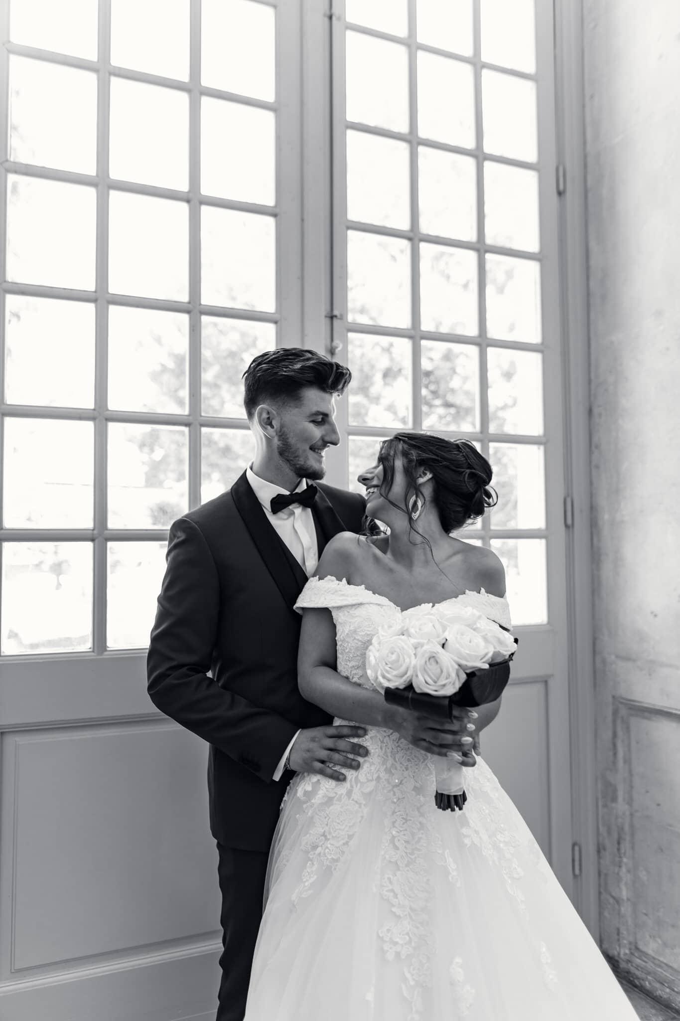 Photo de mariage de mariés qui se regarder et qui posent devant une fenêtre