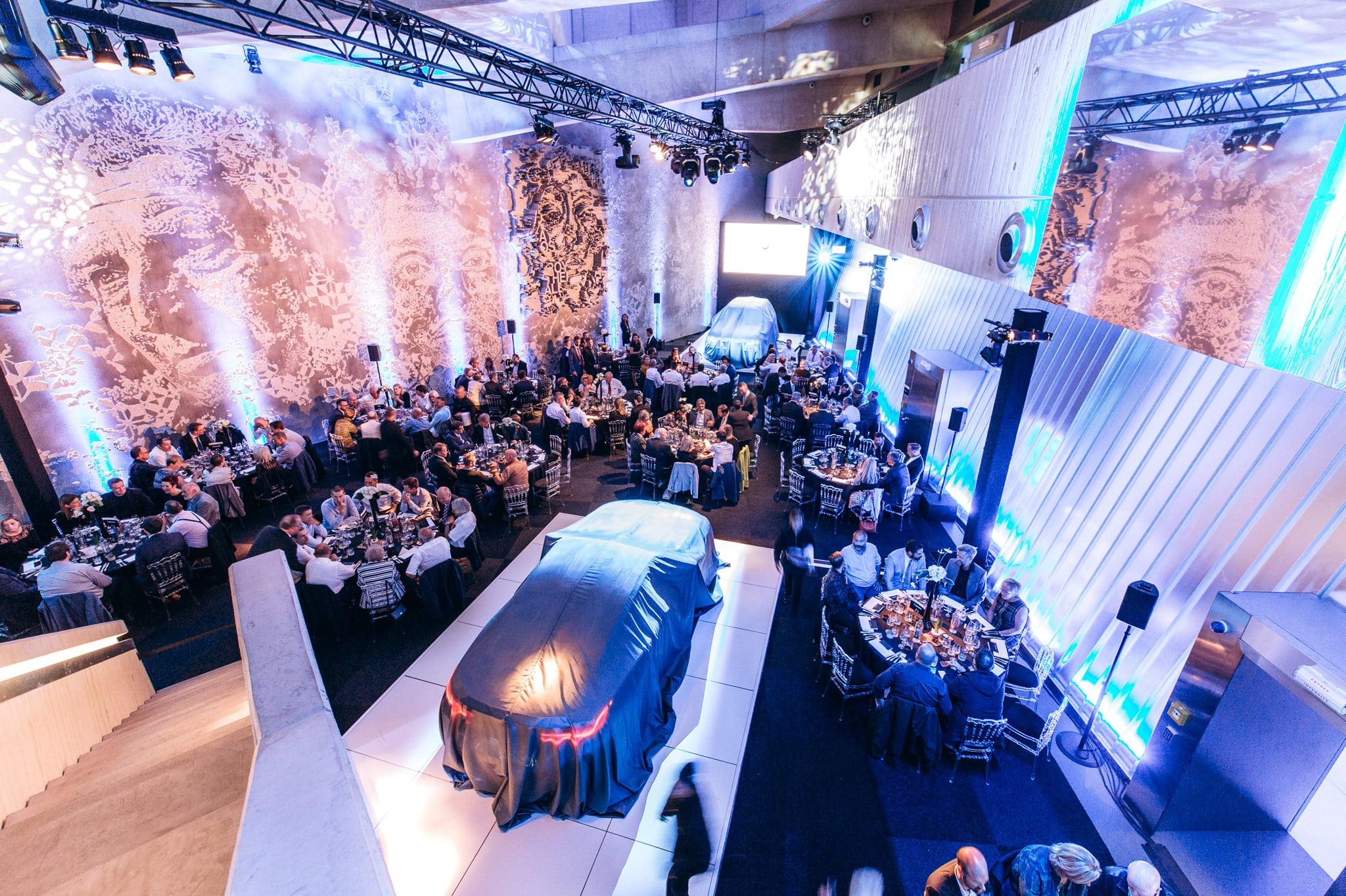 Photo d'entreprise montrant une salle de réception lors d'un meeting BMW avec 2 nouvelles voitures dévoilées.
