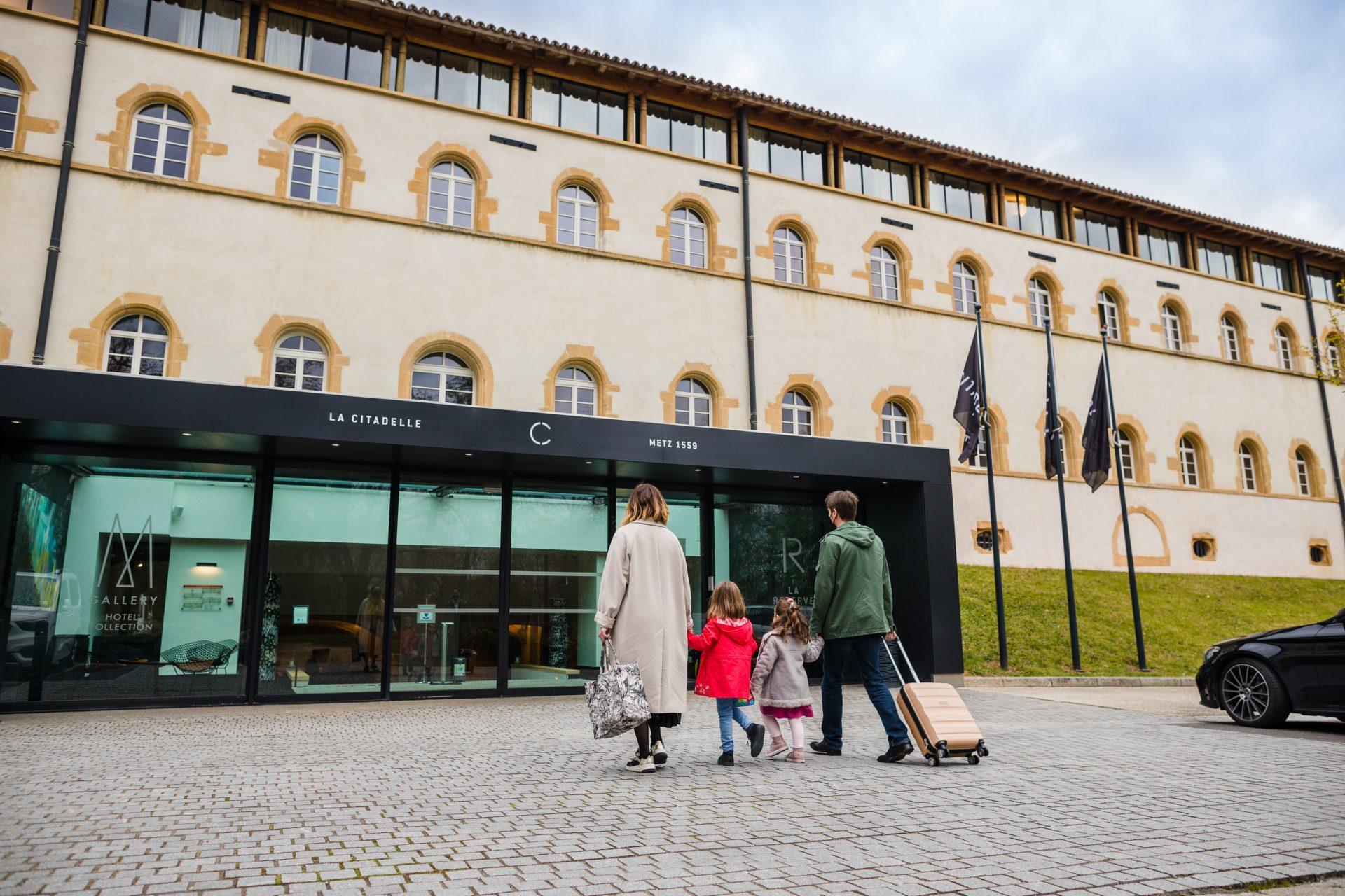 Photo d'entreprise d'une famille entrant dans un hôtel avec leurs bagages