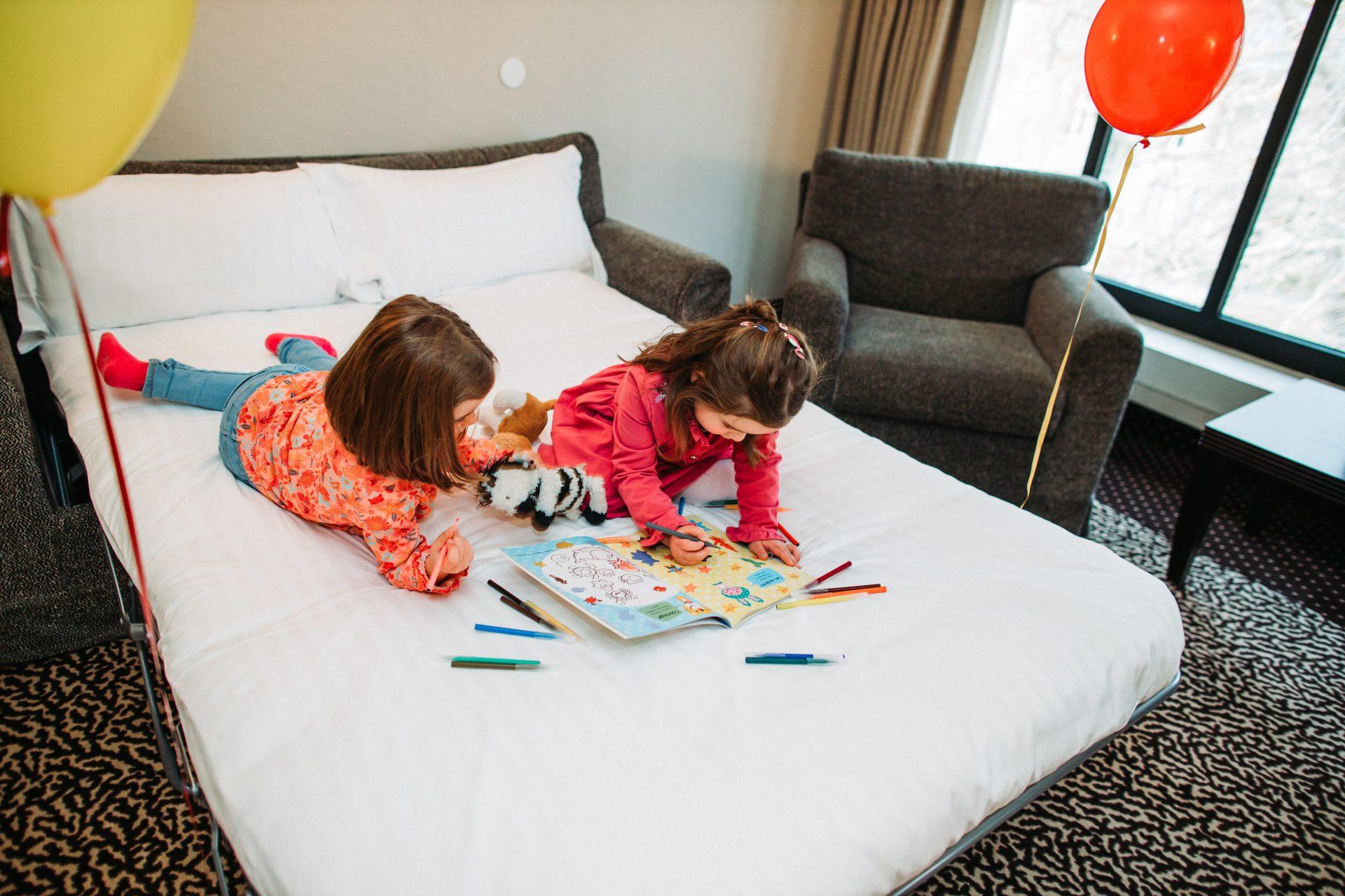 Campagne publicitaire pour un hôtel. Deux enfants dessinent sur un lit.